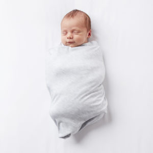 A happy baby swaddled in a gray BreathableBaby Active Swaddle blanket